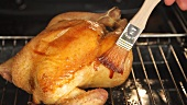 Roast chicken being brushed with spiced butter