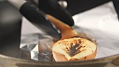 Half an onion being fried in a pan lined with aluminium foil