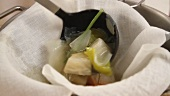 Chicken stock being sieved