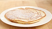Pancakes being dusted with icing sugar