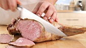 A pink leg of lamb being sliced