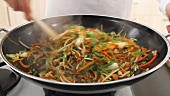 Stir-frying vegetables in a wok