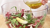 Dressing being poured over a mixed leaf salad
