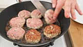 Burgers being turned in a pan