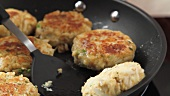 Crab cakes being fried in a pan