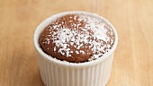 Chocolate souffle being dusted with icing sugar