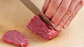 Fresh beef fillet being sliced thinly