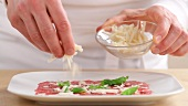 Beef carpaccio being sprinkled with freshly grated parmesan