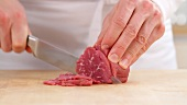 Frozen beef fillet being finely sliced
