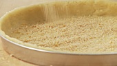 A shortbread base being sprinkled with breadcrumbs