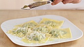 Cooked ravioli being sprinkled with Parmesan cheese