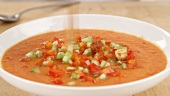 Croutons being sprinkled onto gazpacho