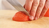 A peeled tomato quarter being diced