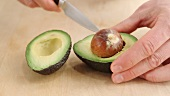An avocado being pitted