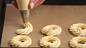 Biscuit rings being piped onto a baking tray lined with greaseproof paper