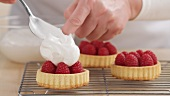 Meringue being spread onto raspberry tartlets