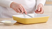 A baking dish being brushed with butter
