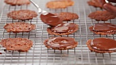 Florentines being spread with chocolate glaze
