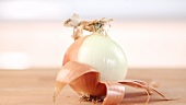 An onion being peeled and halved