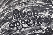 The words 'Buon appetito' written in flour (stop motion)
