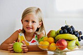 Little girl and full fruit bowl