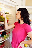 Young woman in front of open refrigerator