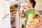 Junger Mann räumt Kühlschrank ein