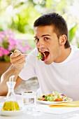 Young man eating salad