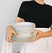 Waitress with stack of plates