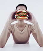 Young woman holding burger in front of face