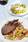 New York steak with vegetables and salad