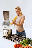 Young, blonde woman cooking