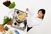 Junge Frau beim Abtropfen von Spaghetti