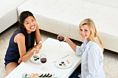 Two young women eating sushi in living room
