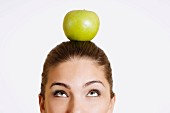 Young woman with an apple on her head