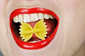 Woman with uncooked farfalle in her mouth