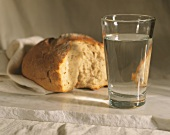 A Loaf of Torn Bread and a Glass of Water