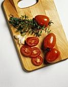 Plum Tomatoes on Cutting Board; Garlic and Oregano