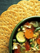 A Bowl of Vegetable Noodle Soup with Crackers