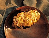 Baked Potato (Süsskartoffel) mit Käse auf braunem Teller