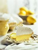 Lemon Meringue PieSlice with Whole Pie and Bowl of Lemons