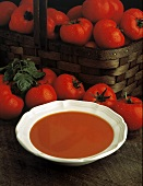 Bowl of tomato soup with basket of whole tomatoes