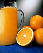 A Cold Pitcher of Orange Juice wirh Fresh Oranges