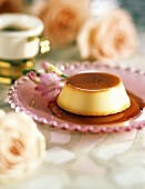 Crème caramel with sauce on a pink glass plate; decoration: flowers