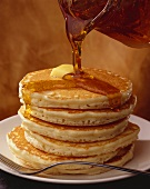 Stack of Pancakes with Syrup Pouring from Pitcher