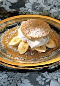 Bananas and whipped cream with a puff pastry top and caramel sauce