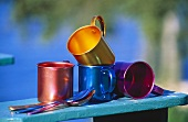 Colorful Tin Cups on the Arm of a Chair
