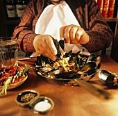 Mann isst Miesmuscheln auf Linguine (hält Muschel in Hand)