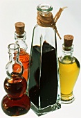Four Assorted Vinegars and Oils in Glass Bottles