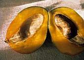 Zwei Mangohälften, eine davon mit Kern